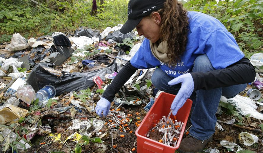 In this Nov. 8, 2017 photo, Steph Gaspar, a volunteer outreach worker with The Hand Up Project, an addiction and homeless advocacy group, cleans up needles used for drug injection that were found at a homeless encampment in Everett, Wash. The number of unsheltered chronically homeless with a serious mental illness, substance use disorder or physical disability has grown steadily in the Everett region, more than doubling since 2015. (AP Photo/Ted S. Warren)