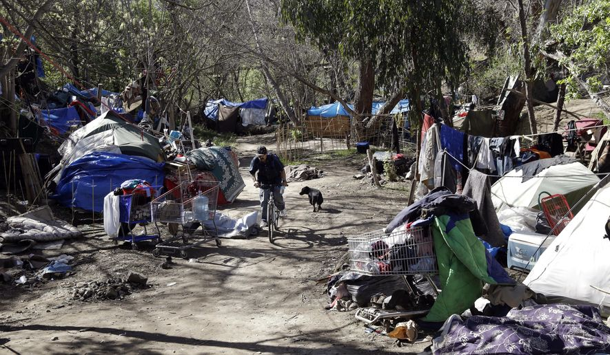 File - This March 11, 2014, file photo shows tents set up along a pathway in the Jungle, a homeless encampment in San Jose, Calif. Officials in San Jose, California have approved a pilot program to build 40 so-called tiny homes for homeless people to address a growing problem in one of the most expensive rental markets in the country. At a meeting Tuesday, Dec. 12, 2017, the city council voted 9-2 to approve the plan to build micro sleeping cabins, which could eventually be expanded to include all 10 council districts.(AP Photo/Marcio Jose Sanchez, File)