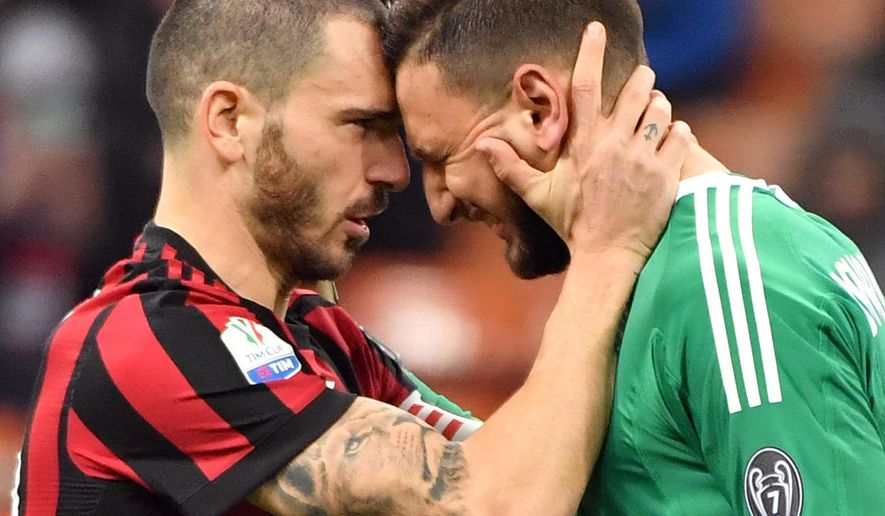 AC Milan's Leonardo Bonucci, left, consoles goalkeeper Gianluigi Donnarumma during the Italian Cup soccer match between AC Milan and Hellas Verona, at the Milan San Siro stadium, Italy, Wednesday, Dec. 13, 2017. (Daniel Dal Zennaro/ANSA via AP)