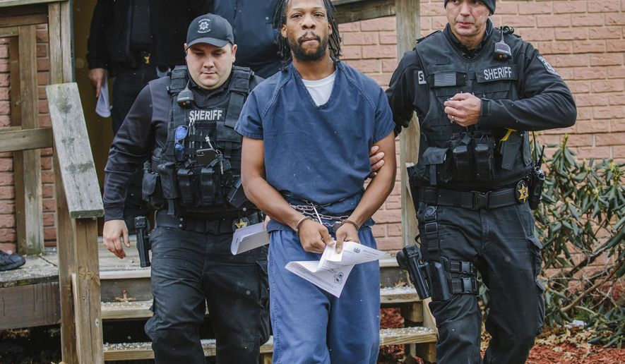 Rahmael Holt, a suspect in New Kensington Officer Brian Shaw's death, is lead from Magisterial District Judge Frank J. Pallone Jr.'s office on Wednesday, Dec. 13, 2017, in New Kensington, Pa. The 29-year-old Natrona Heights man was ordered to stand trial after a preliminary hearing. (Andrew Rush/Pittsburgh Post-Gazette via AP)