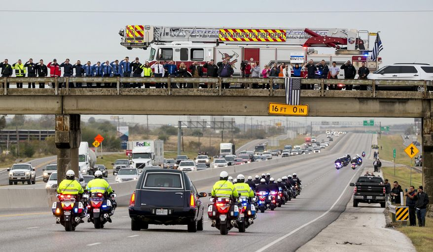 People salute as the funeral procession for San Marcos Police officer Kenneth Copeland passes on Interstate 35 in San Marcos, Texas, on Wednesday, Dec. 13, 2017. Copeland was fatally shot last week while trying to serve a warrant on a domestic violence suspect. (Jay Janner/Austin American-Statesman via AP)
