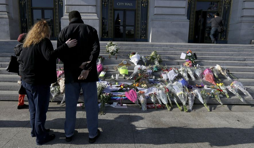 A woman and man pause to look at a memorial for Mayor Ed Lee on the steps of City Hall in San Francisco, Wednesday, Dec. 13, 2017. Lee died Tuesday at 65 after collapsing while grocery shopping. (AP Photo/Jeff Chiu)