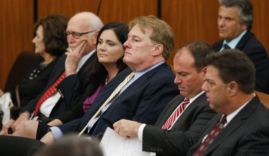 FILE - In an Oct. 24, 2017 file photo, South Carolina Rep Rick Quinn, center, sits with his wife, Amy McRae Benck, his parents, Richard Quinn, Sr. and Ruth LeJeune Quinn, left, and Matthew Richardson and Tracy Edge, right, during bond court in Columbia, S.C. Quinn is resigning Wednesday, Dec. 13, 2017, an hour before a hearing in a Statehouse corruption probe that has ensnared him along with several other lawmakers.  (Tracy Glantz/The State via AP, File)