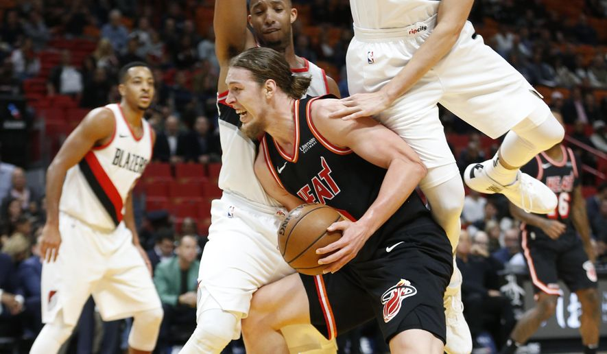 Miami Heat forward Kelly Olynyk, center, attempts a shot against Portland Trail Blazers center Zach Collins, right, and guard Evan Turner, left, during the first half of an NBA basketball game, Wednesday, Dec. 13, 2017, in Miami. (AP Photo/Wilfredo Lee)