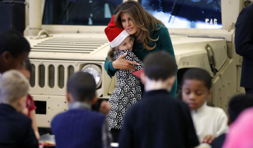 "First lady Melania Trump hugs the child of a military family, Wednesday, Dec. 13, 2017, during a ""Toys for Tots"" event at Joint Base Anacostia-Bolling in Washington. (AP Photo/Jacquelyn Martin)"