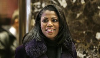 Omarosa Manigault smiles at reporters as she walks through the lobby of Trump Tower in New York. (AP Photo/Seth Wenig) ** FILE **