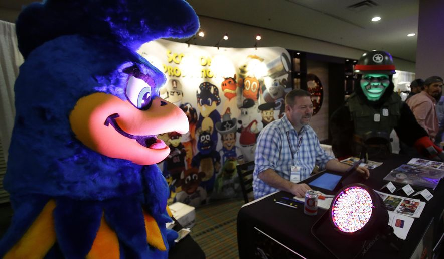Rick Scollon of Scollon Mascots and Characters, Inc. works his booth at a trade show at the Major League Baseball winter meetings Wednesday, Dec. 13, 2017, in Orlando, Fla. (AP Photo/John Raoux)