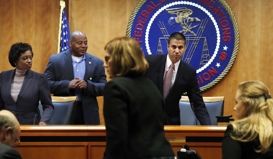 Federal Communications Commission (FCC) Chairman Ajit Pai (right) and Commissioner Mignon Clyburn (far left) were asked to leave by a member of security as the meeting room is evacuated where the Federal Communications Commission was about to vote on net neutrality Thursday. (Associated Press)