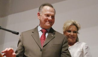 Republican Senate candidate Roy Moore walks off the stage with wife Kayla Moore after he spoke to supporters after an election-night watch party at the RSA activity center, Tuesday, Dec. 12, 2017, in Montgomery, Ala. Moore didn't concede the election to Democrat Doug Jones. (AP Photo/Brynn Anderson)