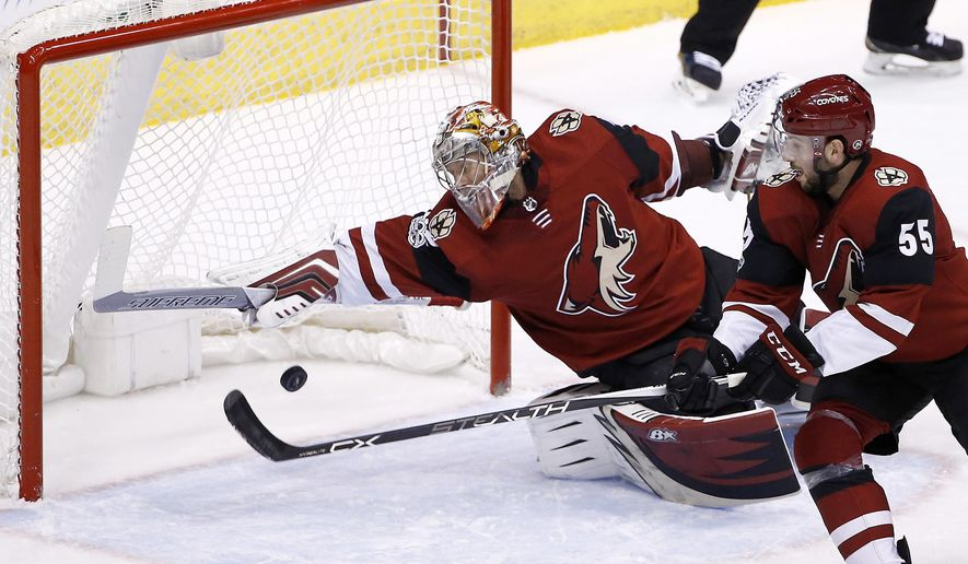 Arizona Coyotes goalie Antti Raanta (32) makes a diving save against the Tampa Bay Lightning as Coyotes defenseman Jason Demers (55) looks on during the first period of an NHL hockey game, Thursday, Dec. 14, 2017, in Glendale, Ariz. (AP Photo/Ross D. Franklin)