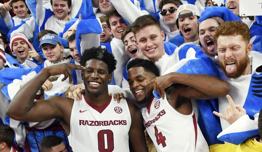 FILE - In this Friday, Dec. 9, 2017, file photo, Arkansas players Jaylen Barford (0) and Daryl Macon (4) celebrate with fans after beating Minnesota after the second half of an NCAA college basketball game in Fayetteville, Ark. Led by the senior guard duo of Barford and Macon, along with talented freshman Daniel Gafford, the surging Razorbacks are dominating, winning their games by an average of 23 points per game and nearing a return to the rankings for the first time since 2015. (AP Photo/Michael Woods, File)