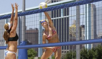 FILE - In this July 16, 2015 file photo, Carol Welcher, right, tries to get the ball over the net in front of Jennifer Henderson during an Association of Volleyball Professionals qualifying tournament, with a view of the Manhattan skyline, in the Brooklyn borough of New York. Amazon has an agreement with the AVP tour to livestream almost every match from every tournament for the next three summers. The deal announced Thursday, Dec. 14, 2017,  could provide a boost for a sport that emerges as an Olympic favorite for American TV audiences every four years but has struggled to sustain viewership.  (AP Photo/Seth Wenig, File)