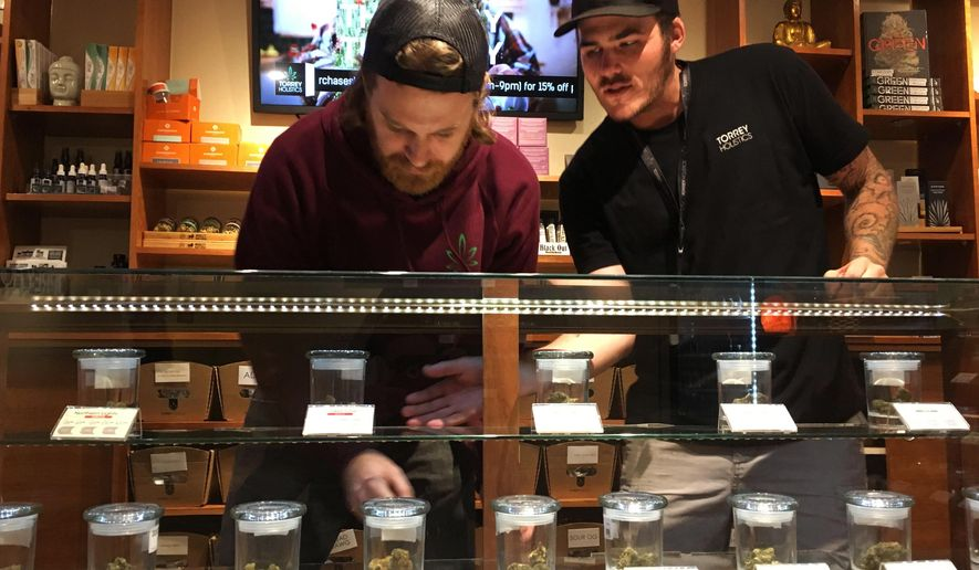 Torrey Holistics employees, Matt Sullivan, left, and Taron McElroy, arrange jars of cannabis in San Diego, Calif., Thursday, Dec. 14, 2017.  On Thursday, California issued its first batch of business licenses for the state's upcoming legal marijuana market, setting the stage for sales to begin to adults in January. The first license for recreational retail sales went to Torrey Holistics in San Diego. (AP Photo/Julie Watson)