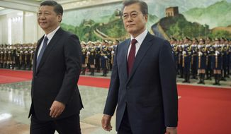 South Korean President Moon Jae-In, right, and Chinese President Xi Jinping review the Chinese honor guard during a welcome ceremony at the Great Hall of the People in Beijing, Thursday, Dec. 14, 2017. (Nicolas Asfouri/Pool Photo via AP)