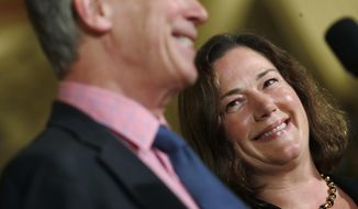 Melissa Hart, back, a University of Colorado law professor, smiles as she is introduced by Colorado Gov. John Hickenlooper as the newest member of the Colorado Supreme Court Wednesday, Dec. 14, 2017, during a news conference in the State Capitol in Denver. Hart will take the place of Allison Eid, who was appointed to Denver's federal appeals court, on the state's seven-member Supreme Court. (AP Photo/David Zalubowski)