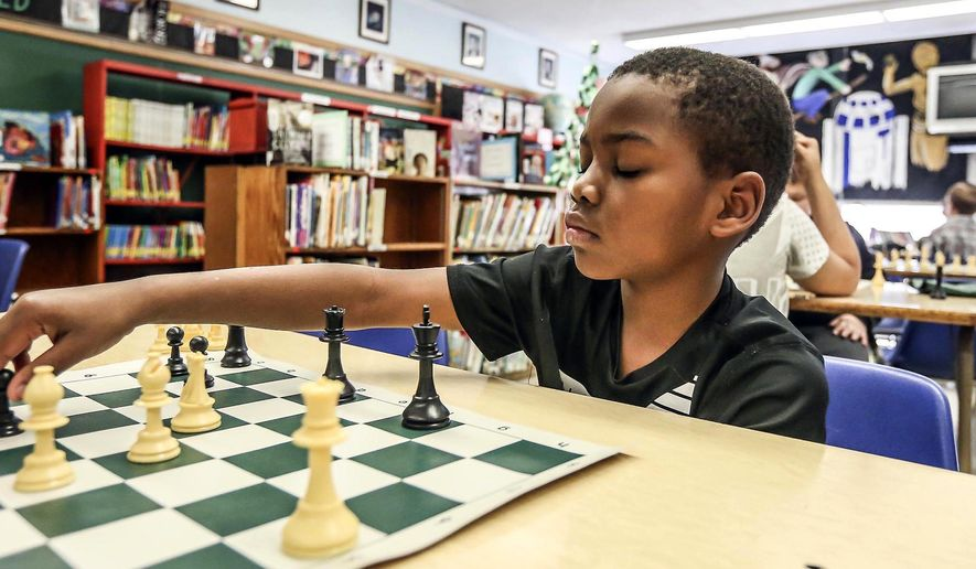 In this Dec. 1, 2017 photo,second-grader Kaylen Williams ponders what move to do next  during chess after school at South Shores Elementary School in Decatur, Ill. (Clay Jackson/Herald & Review via AP)