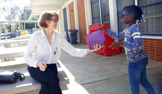 """ADVANCE FOR USE SUNDAY, DEC. 17 - In this Nov. 28, 2017 photo, Kalese Seamore, 9, a third grader at Terwilliger Elementary, hands her lunch to her """"lunch buddy"""" Laura Clark, a volunteer in the Alachua County Public Schools program Lunch Buddies, during lunch at the school in Gainesville, Fla. The mentoring program for elementary school students, Lunch Buddies, asks volunteers once a week to visit with their student and talk about their lives, the day or whatever comes up. (Brad McClenny/Star-Banner via AP)"""