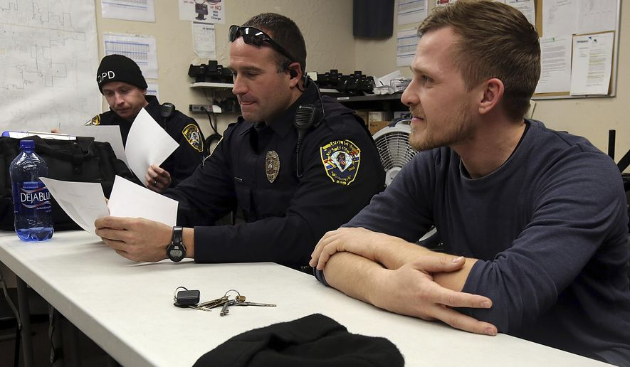 In this Dec. 5, 2017 photo, Stefan Schott, right, a police officer from Germany, sits with his  partner, Quincy Police Officer J.D. Summers, center, before a briefing at Quincy Police Department in Quincy Ill. Schott has been working as an intern with the department since November 20th and his last day was be Dec. 6, 2017. Eddie Bogue, police chief in Palmyra, Mo., was responsible for pairing Schott with the Quincy police. (Phil Carlson/The Quincy Herald-Whig via AP)/