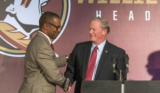 In this Wednesday, Dec. 6, 2017 photo, Willie Taggart, left, is greeted by Florida State University president John Thrasher before as Taggart is introduced as the Seminoles' coach during an NCAA college football news conference in Tallahassee, Fla. (AP Photo/Mark Wallheiser)