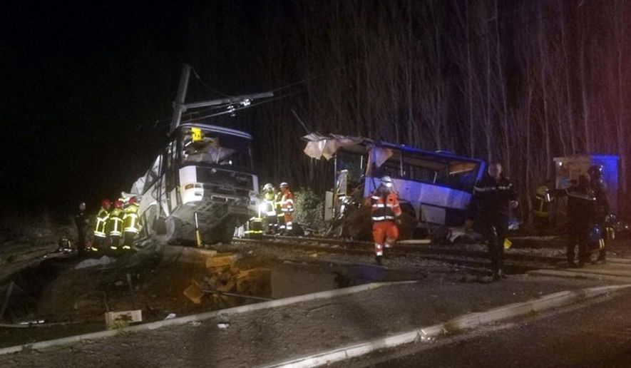 In this photo provided by France Bleu, rescue workers help after a school bus and a regional train collided in the village of Millas, southern France, Thursday, Dec. 14, 2017. A school bus and a regional train collided in southern France on Thursday, killing four children and critically injuring several other people on the bus, the French interior ministry said. (Matthieu Ferri/France Bleu via AP)