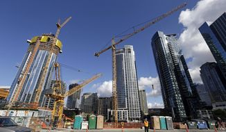 FILE - In this Wednesday, Oct. 11, 2017, file photo, construction cranes fill a block across from an Amazon building in Seattle. Seattle is among a fistful of cities that have flourished in the 10 years since the Great Recession officially began in December 2007, even while most other large cities, and sizable swaths of rural America, have managed only modest recoveries. (AP Photo/Elaine Thompson, File)