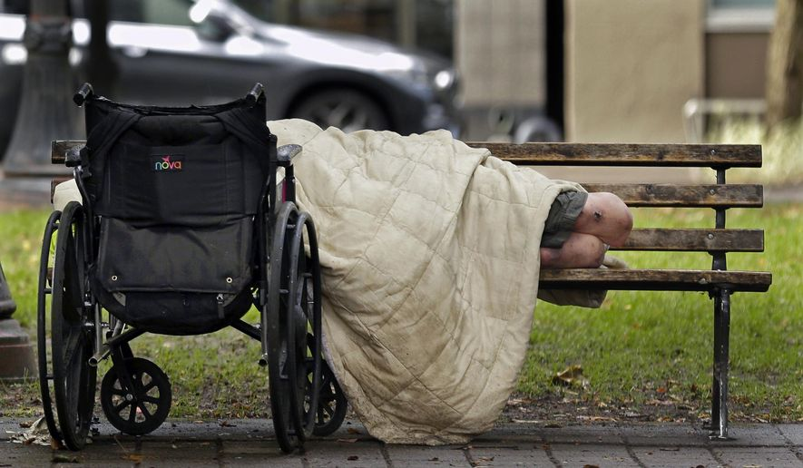 FILE - In this Sept. 19, 2017, file photo, a person sleeps next to a wheelchair on a park bench in downtown Portland, Ore., not far from the city's trendy Pearl District. An annual report found that 80 homeless people died on the streets of Portland and the surrounding area in 2016. The number released Thursday, Dec. 14 is only a slight improvement over 2015, when 88 homeless people died outside. (AP Photo/Ted S. Warren, File)