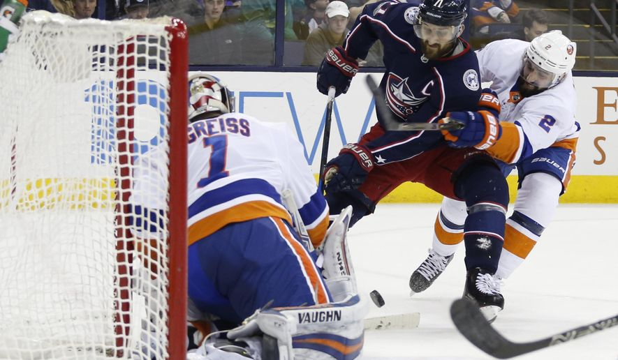 New York Islanders' Thomas Greiss, left, of Germany, protects the goal as teammate Nick Leddy, right, tries to take the puck away from Columbus Blue Jackets' Nick Foligno during the second period of an NHL hockey game Thursday, Dec. 14, 2017, in Columbus, Ohio. (AP Photo/Jay LaPrete)