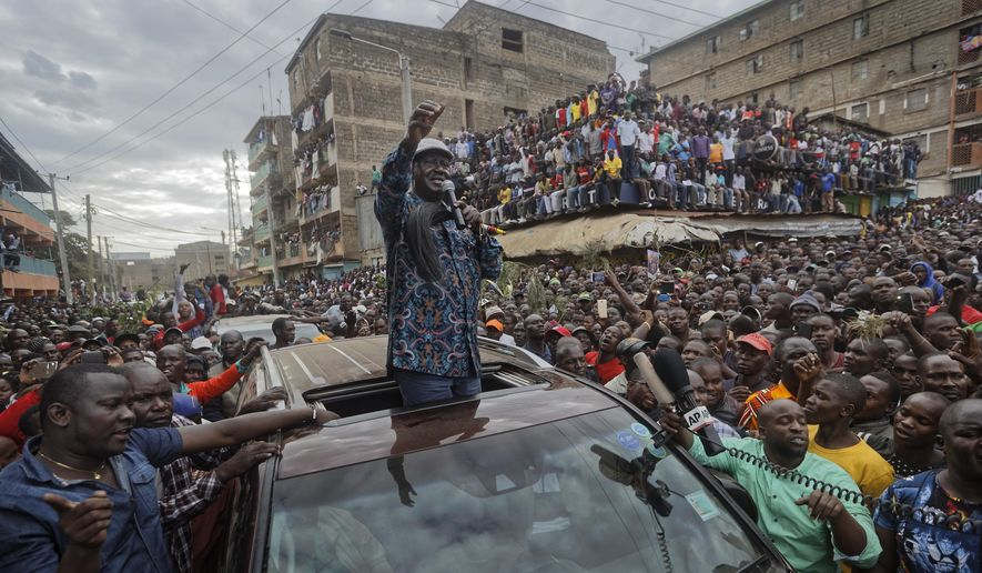 FILE - In this Sunday, Aug. 13, 2017 file photo, Kenyan opposition leader Raila Odinga gestures to thousands of supporters gathered in the Mathare slum of Nairobi, Kenya. A privacy watchdog said Thursday, Dec. 14, 2017 that Kenya's opposition leader Raila Odinga was targeted by a virulent online campaign created by a Texas-based company during the recent election turmoil. (AP Photo/Ben Curtis, File)