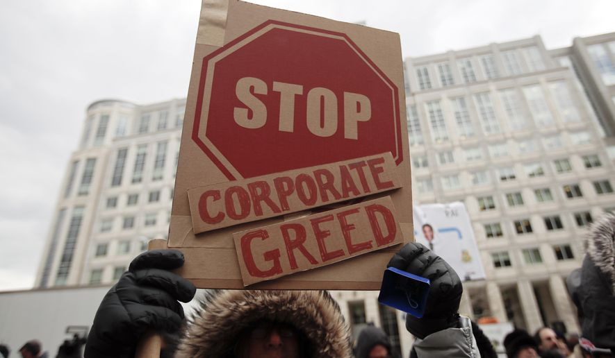 "A woman hold a sign that reads ""Stop Corporate Greed"" during a protest at the Federal Communications Commission (FCC), in Washington, Thursday, Dec. 14, 2017, where the FCC is scheduled to meet and vote on net neutrality. The vote scheduled today at the FCC, could usher in big changes in how Americans use the internet, a radical departure from more than a decade of federal oversight. (AP Photo/Carolyn Kaster) **FILE**"