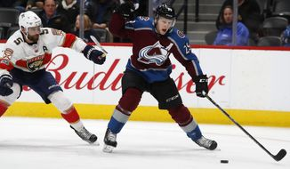 Colorado Avalanche center Nathan MacKinnon, right, drives past Florida Panthers defenseman Aaron Ekblad on the way to scoring the go-ahead goal in the third period of an NHL hockey game Thursday, Dec. 14, 2017, in Denver. (AP Photo/David Zalubowski)