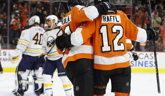 Philadelphia Flyers' Valtteri Filppula, center, of Finland, celebrates his goal with Michael Raffl, right, of Austria, on Buffalo Sabres' Robin Lehner, left, of Sweden, during the second period of an NHL hockey game, Thursday, Dec. 14, 2017, in Philadelphia. (AP Photo/Chris Szagola)