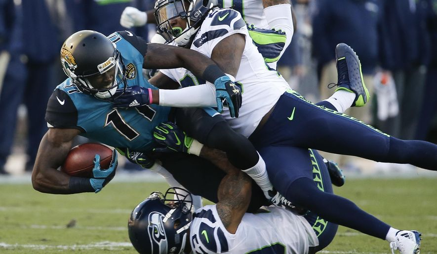 Jacksonville Jaguars wide receiver Marqise Lee (11) is tackled by Seattle Seahawks cornerback Shaquill Griffin, top right, and safety Earl Thomas, bottom, after a reception during the first half of an NFL football game, Sunday, Dec. 10, 2017, in Jacksonville, Fla. (AP Photo/Stephen B. Morton)