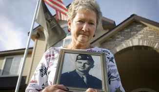 Jorja Reyburn stands with a photo of her father,  1st Lt. James Elliott, who went missing in the Korean War when she was two years old, in front of her Boise, Idaho home. She says the family will continue the search no matter what. (Katherine Jones/Idaho Statesman via AP)