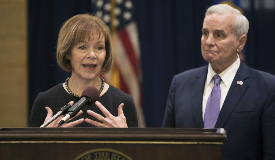 Minnesota Gov. Mark Dayton listens to Lt. Gov. Tina Smith during a news conference, as she was named to replace fellow Democrat Al Franken in the U.S. Senate on Wednesday, Dec. 13, 2017 in St. Paul, Minn.  Franken announced his resignation last week amid growing sexual misconduct allegations.  (Brian Peterson/Star Tribune via AP)