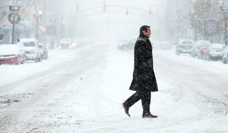A man casually walks across a nearly barren street during a heavy snowstorm on Wednesday, Dec. 13, 2017 in downtown Flint, Mich. (Jake May/The Flint Journal-MLive.com via AP)