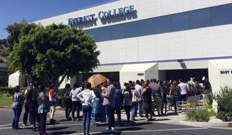FILE - In this April 28, 2015, file photo, students wait outside Everest College in Industry, Calif., hoping to get their transcriptions and information on loan forgiveness and transferring credits to other schools. California's attorney general is suing the Trump administration, saying the federal Department of Education is refusing to process debt relief claims from tens of thousands of students who had federal loans to attend Corinthian Colleges. (AP Photo/Christine Armario, File)