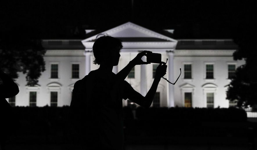 FILE - In this Aug. 25, 2017, file photo, a tourist takes a photo from Pennsylvania Avenue of the illuminated White House in Washington. The White House is embarking on a major campaign to turn public opinion against the nation's largely family-based immigration system ahead of an all-out push next year to move toward a more merit-based structure. (AP Photo/Carolyn Kaster, File)