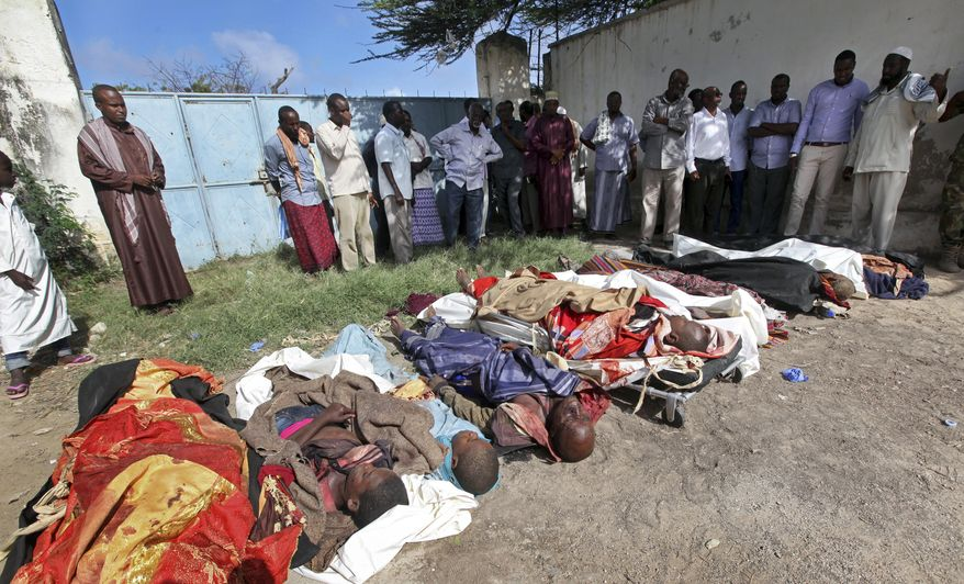 FILE - In this Friday, Aug. 25, 2017 file photo, Somalis observe bodies which were brought to and displayed in the capital Mogadishu, Somalia, following a raid by foreign and Somali forces on a farm in Bariire village in southern Somalia. A spokesman for U.S. Africa Command said Wednesday, Dec. 13, 2017 that its head Marine Gen. Thomas Waldhauser has asked the Naval Criminal Investigative Service to look into whether civilians were killed during the raid by Somali troops supported by U.S. special operations forces. (AP Photo/Farah Abdi Warsameh, File)