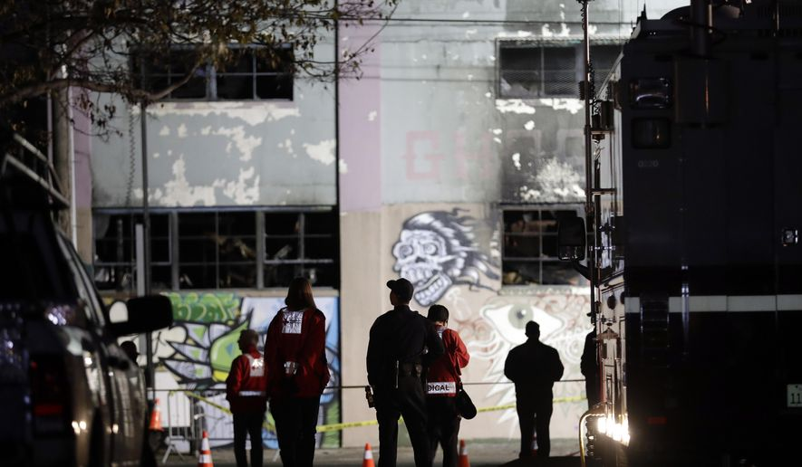 FILE - In this Dec. 5, 2016, file photo, emergency crews stand in front of the site of a warehouse fire in Oakland, Calif. A fire department captain said during a court hearing on Tuesday, Dec. 12, 2017, that one of the men charged in a warehouse fire in California that killed 36 people told him no one lived in the building during a September 2014. (AP Photo/Marcio Jose Sanchez, File)