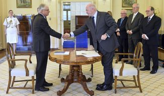 In this photo provided by the Australian Government Royal Commission, Commissioner Justice Peter McClellan, second left, shakes hands with Governor-General of Australia Peter Cosgrove, fourth right, at the signing ceremony and the release of the final report of the Royal Commission into Institutional Responses to Child Sexual Abuse at Government House, in Canberra, Dec. 15, 2017. The commission delivered its final 17-volume report and 189 recommendations following a wide-ranging investigation. (Jeremy Piper/Australian Government Royal Commission via AP)