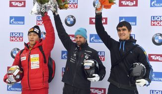 Latvia's winner Martins Dukurs, center, South Korea's second placed Yun Sung-bin, left, and Russia's third placed Nikita Tregubov celebrate on the podium after the men's Skeleton World Cup race in Innsbruck, Austria, Friday, Dec. 15, 2017. (AP Photo/Kerstin Joensson)