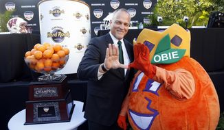 "FILE - In this Wednesday, Dec. 6, 2017, file photo, Miami head coach Mark Richt, left, helps Orange Bowl mascot Obie make the Miami ""U"" symbol as they pose for photos after a news conference, in Hollywood, Fla. FAU, Miami, Navy and Memphis are playing their bowl games on their home fields, and five other teams will play bowls in their home states. And that number could rise to six if Georgia makes the College Football Playoff championship game in Atlanta. (AP Photo/Wilfredo Lee, File)"