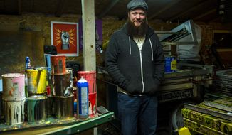In this Tuesday, Nov. 28, 2017 photo, artist Travis Bone poses for a portrait in his workshop in Midvale, Utah. His posters, sold under the brand Furturtle, are often found alongside standard T-shirt options at shows from Red Butte Garden to the Twilight Concert Series to Kilby Court and more. Each poster is unique, designed for a single show. (Chris Detrick/The Salt Lake Tribune via AP)
