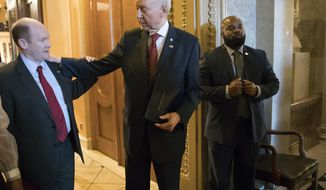 Senate Finance Committee Chairman Orrin Hatch, R-Utah, center, talks with Sen. Chris Coons, D-Del., left, as they leave the chamber following a vote, on Capitol Hill, in Washington, Thursday, Dec. 14, 2017. (AP Photo/J. Scott Applewhite)