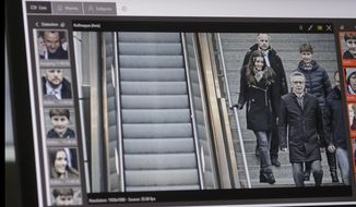 A computer with an automatic facial recognition system shows German Interior Minister Thomas de Maiziere, center right, as he visits the Suedkreuz train station in Berlin, Friday, Dec. 15, 2017. At the train station, German authorities test automatic facial recognition technologies. (AP Photo/Markus Schreiber, pool)