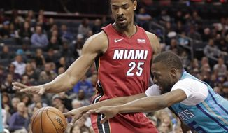 Charlotte Hornets' Kemba Walker (15) and Miami Heat's Jordan Mickey (25) chase the ball during the first half of an NBA basketball game in Charlotte, N.C., Friday, Dec. 15, 2017. (AP Photo/Chuck Burton)