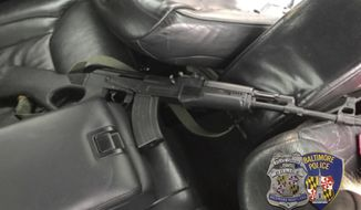 This image made by Baltimore Police chief spokesman T.J. Smith show a weapon inside the car of a shooting suspect in Baltimore, Md., Friday, Dec. 15, 2017. The gunman fleeing police in the car shot wildly at officers and pedestrians across a swath of Baltimore on Friday, as he led cruisers on a chase that looped through streets of the city for at least 20 minutes before he was captured. The gunman injured two people. (T.J. Smith/Baltimore Police Dept. via AP)