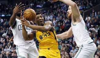 Utah Jazz's Donovan Mitchell (45) drives for the basket between Boston Celtics' Jaylen Brown, left, and Aron Baynes during the second quarter of an NBA basketball game in Boston, Friday, Dec. 15, 2017. (AP Photo/Michael Dwyer)