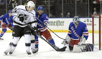 New York Rangers goalie Henrik Lundqvist (30) stops a shot by Los Angeles Kings left wing Jussi Jokinen (36)as he is checked by Rangers defenseman Brendan Smith (42) during the first period of an NHL hockey game Friday, Dec. 15, 2017, at Madison Square Garden in New York. (AP Photo/Bill Kostroun)