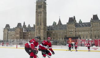 Ottawa Senators left wing Nick Paul, left, and defenseman Fredrik Claesson run a drill as they skate on the ice rink on Parliament Hill, Friday Dec. 15, 2017, in Ottawa. The Senators will play the Montreal Canadiens in the NHL 100 Classic regular season match outdoors on Saturday. (Adrian Wyld/The Canadian Press via AP)